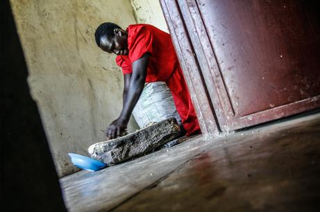 Female former child soldier grinds peanuts