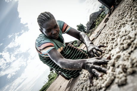 Female former child soldier drying cassava to make alcohol