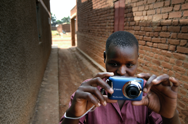 Female former child soldier learning how to use a camera for a new business