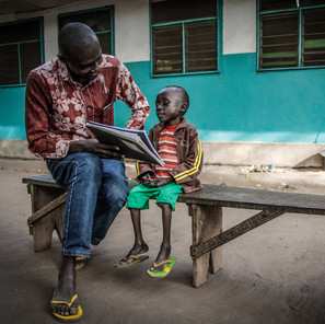 Artist Didier Kassai with young boy suffering from malaria and malnutrition as a result of the ongoing conflict