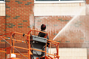 outdoor worker cleaning the exterior wal