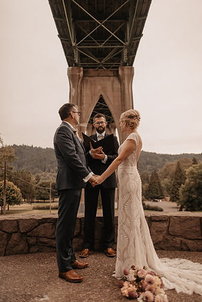 wedding couple and officiant stand under st johns bridge in cathedral park portland oregon for elopement. bride's bouquet sits at her feet