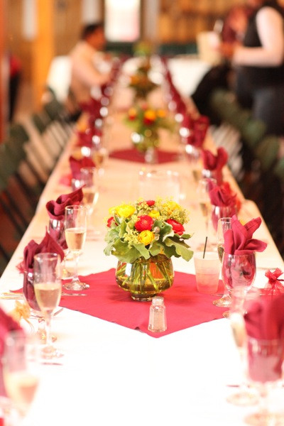 A long wedding banquet table is decorated with autumnal bouquets and napkins.