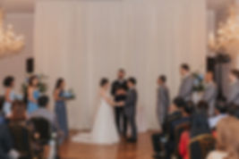 bride and groom stand with officiant and wedding party in a chandelier filled ballroom