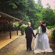 Married couple at their wedding wait to enter their reception. Bride wears a flower crown