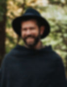 wedding officiant wearing a felt hat and woven cloak stands in the woods and smiles