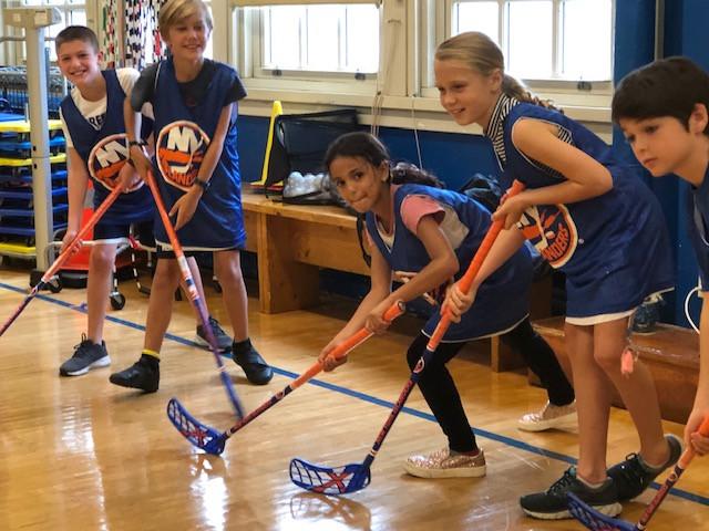 students playing floor hockey
