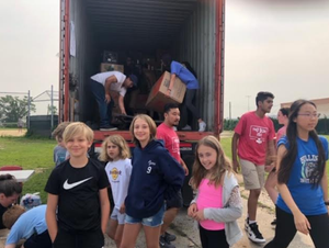 students and families loading boxes into truck