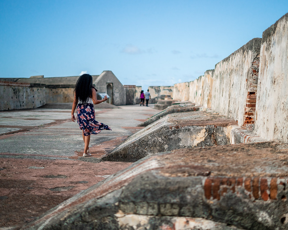 Young Dominican girl with a flower dress walking on el morro de puert rico.