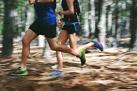 Couple running fast through the forest o