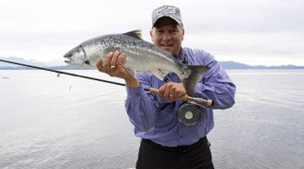 Legacy Lodge guest with fly rod and coho