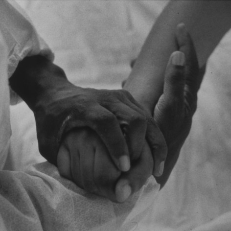 She tightly grasps the hands of her mother, Charmaine Clowney
