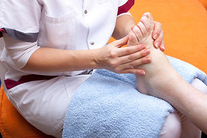pretty  Nurse treats a patient's foot.jp