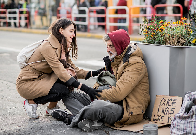 Young woman giving money to homeless beg