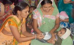 Women Feed a Baby