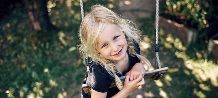 A young girl, around age 7, swings one a backyard swing while looking up and smiling at the camera.