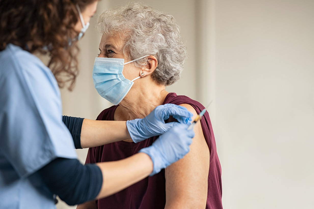 General practitioner vaccinating old pat