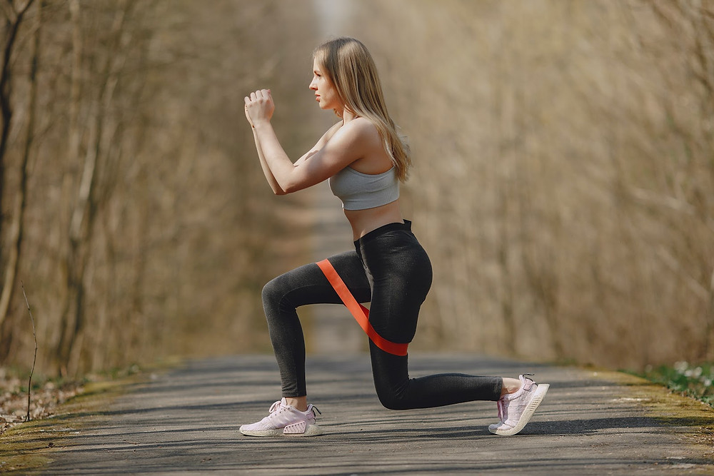 Woman doing lunges with hip resistance band