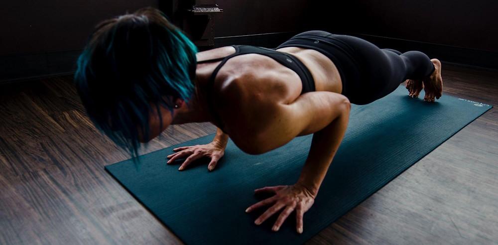 woman doing push-ups on yoga mat