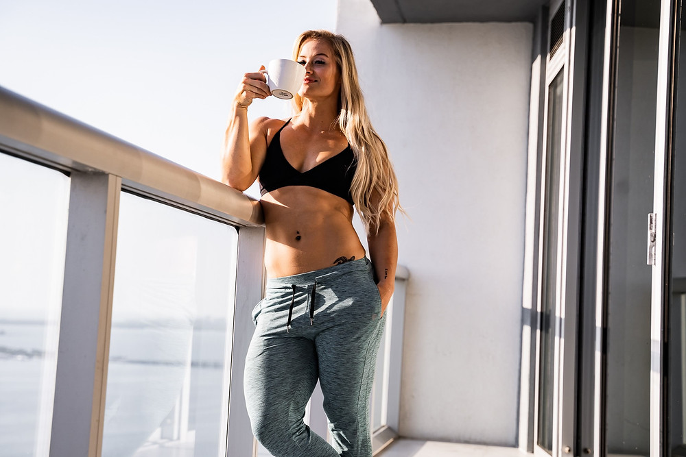 girl in legging drinking coffee on balcony
