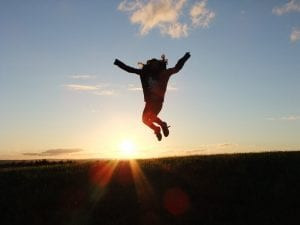woman jumping in the air in front of a sunset