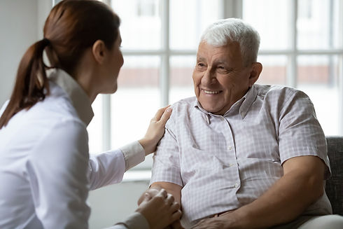 Caring nurse talks to old patient holds
