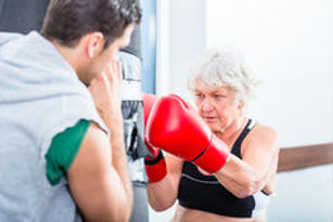 senior-woman-trainer-boxing-sparring-wom