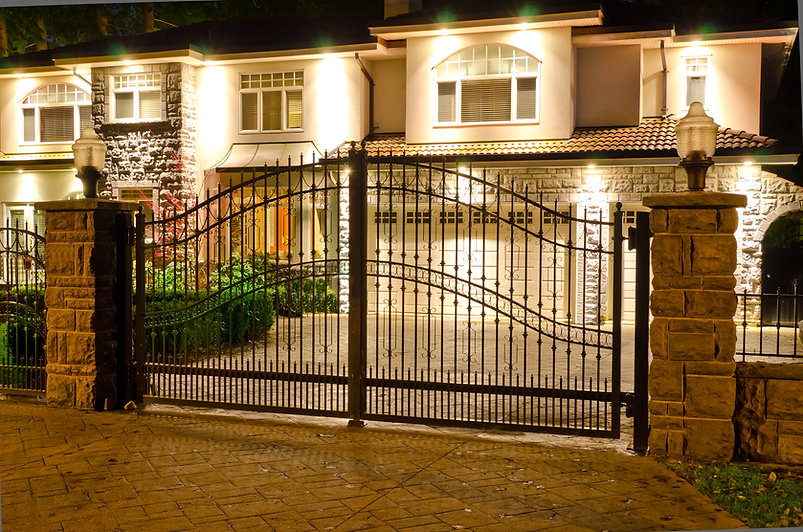A luxury house with the gates in suburbs at dusk in Vancouver, Canada.jpg