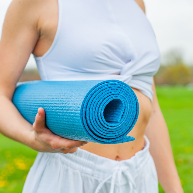 woman-standing-and-holding-blue-yoga-mat