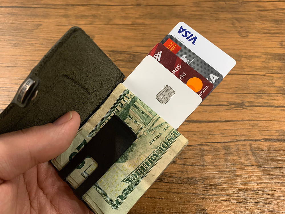 A wallet clip holding cash and a variety of credit cards