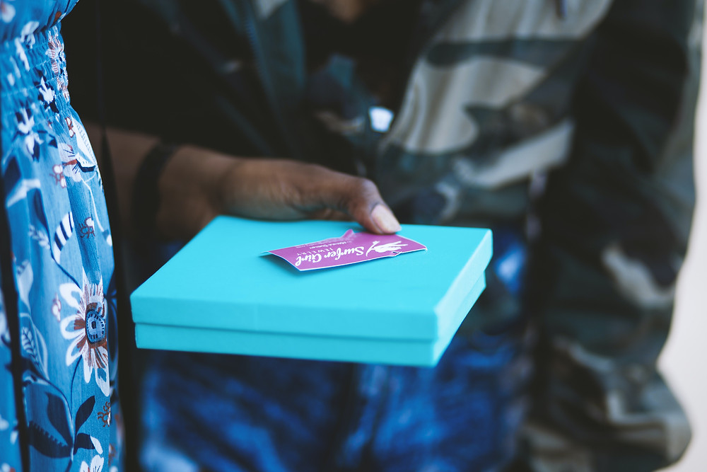 A customer holds a box with a gift card to a local small business