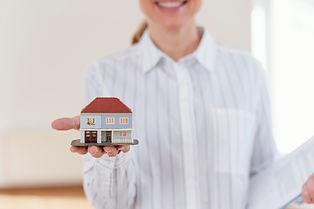 front-view-of-smiley-defocused-female-realtor-showing-miniature-house.jpg