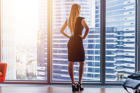 Rear view of elegant female boss standing in modern office looking at skyscrapers through