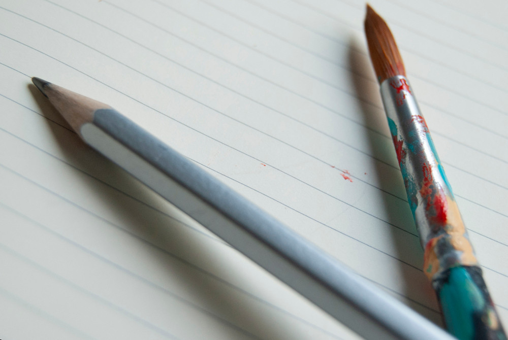A pencil and colourful paint brush point in opposite directions
