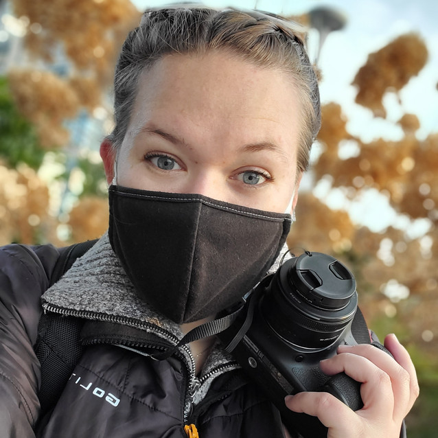 woman holding camera taking a close up selfie with a face mask