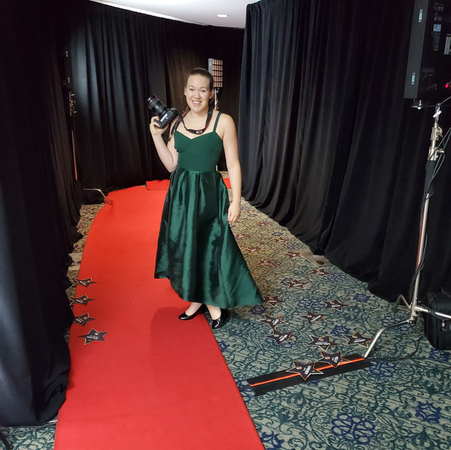 woman in a long green dress holding a camera on an indoor red carpet