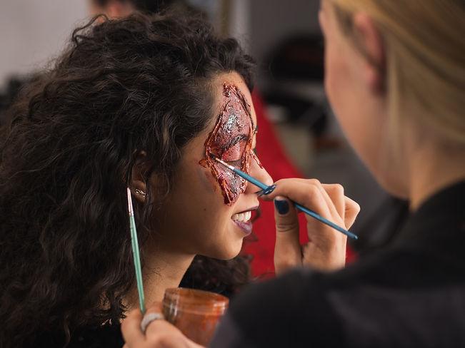 artist-applying-greasepaint-on-female-face-in-dres-FK9Z87E.jpg