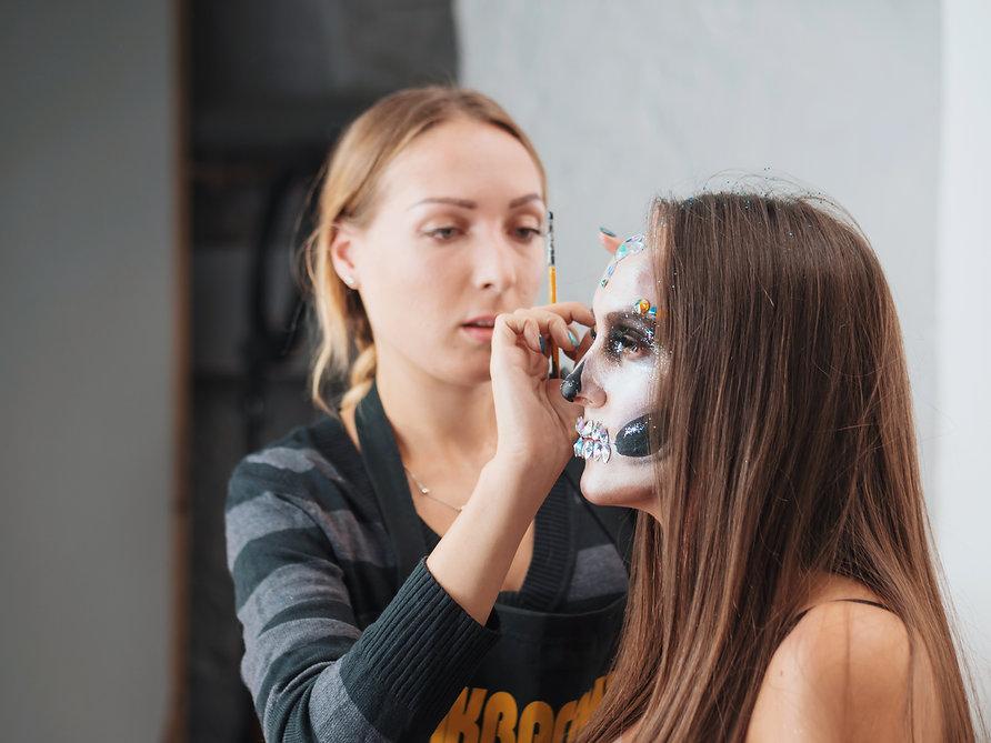 artist-applying-greasepaint-on-female-face-in-dres-98G7K6M.jpg