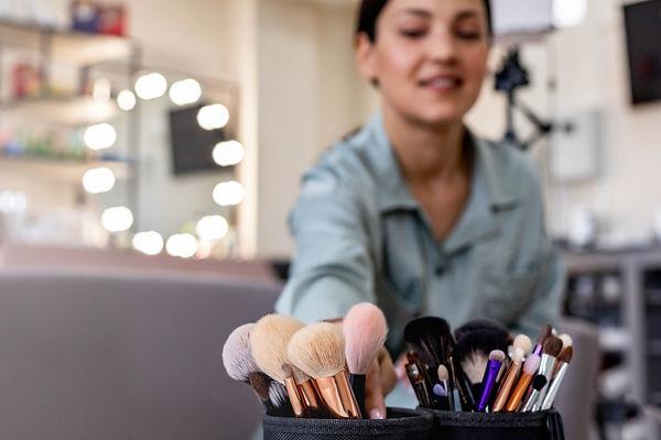 closeup-female-makeup-artist-hands-taking-brush-fo-APT979Z.jpg
