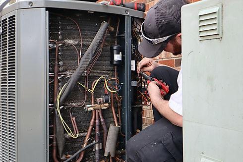 service-repair-being-done-on-a-heat-pump-hvac-syst-CUZ5KG7.jpg