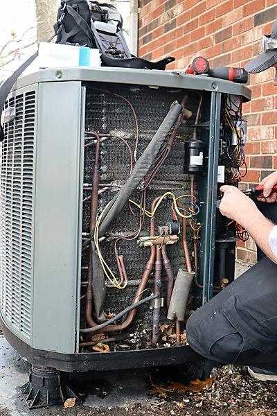 service-repair-being-done-on-a-heat-pump-hvac-syst-UXQR8SZ.jpg