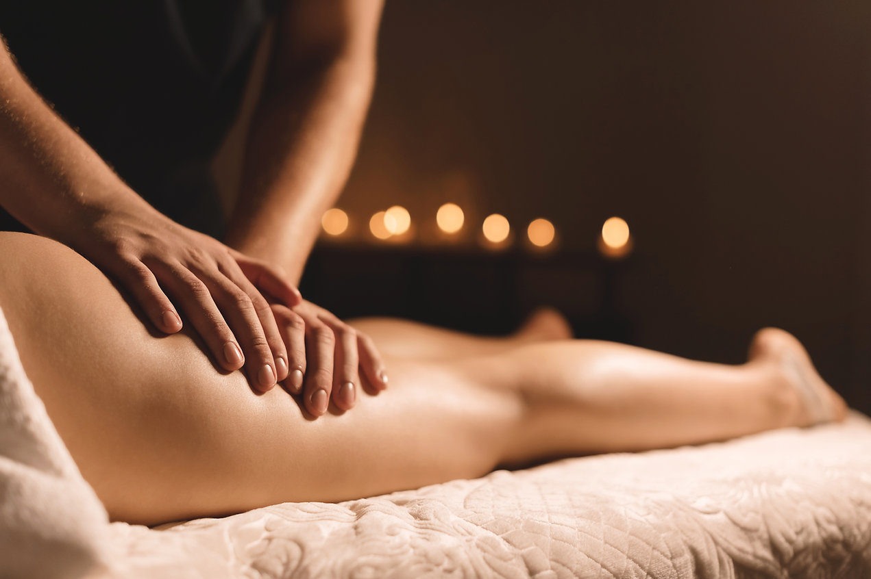 A masseur in a dark room does a hip mass