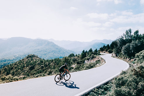 cyclist-riding-bike-sunset-mountain-road.jpg