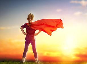 Little child girl plays superhero. Child