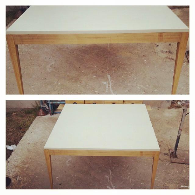 Mesa de 140 x 140 de tabla de microcemento con patas de madera lustrada