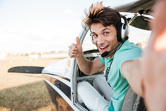 Cheerful excited young pilot sitting in