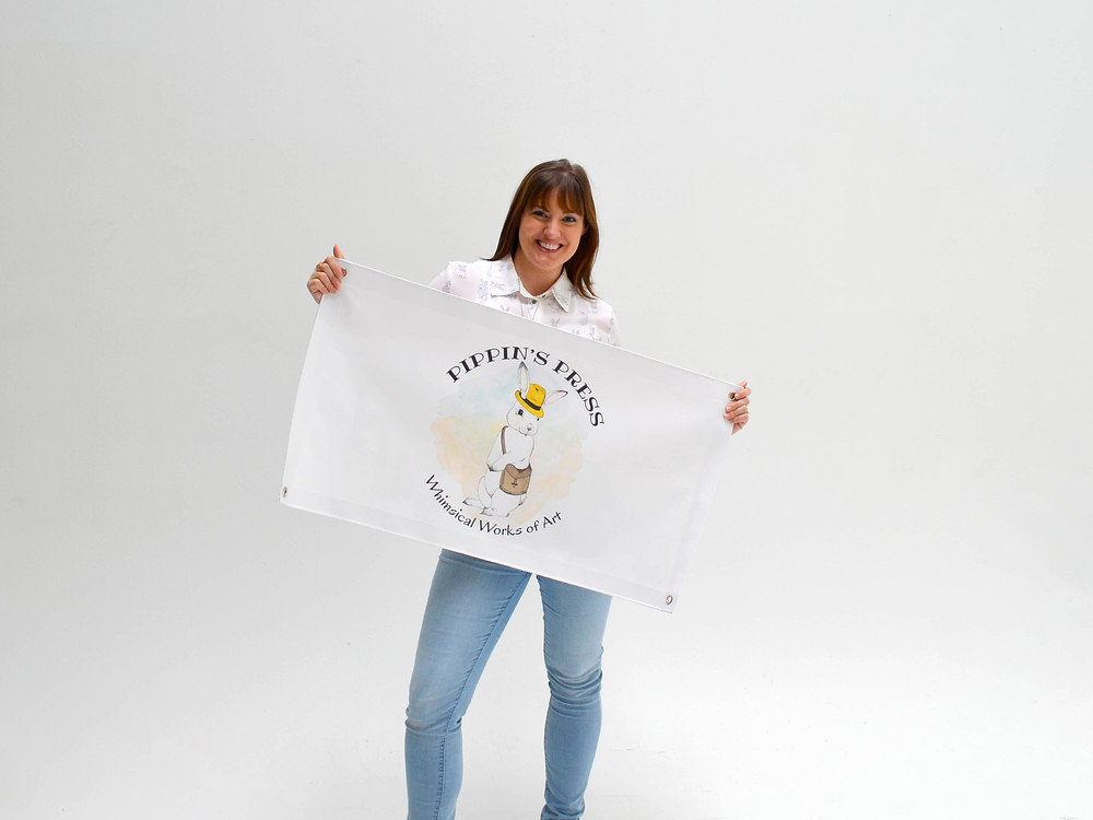 Kyla holding the new Pippin's Press banner during a photoshoot.