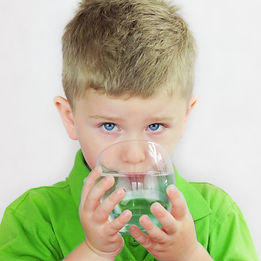 Portrait of boy drinking glass of water.