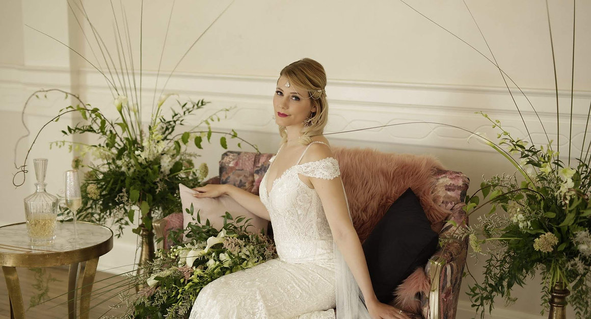 A bride sits on a pink chaise with white flowers.