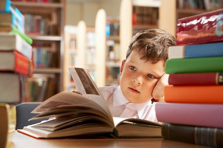 little-boy-studying-in-the-library_1098-